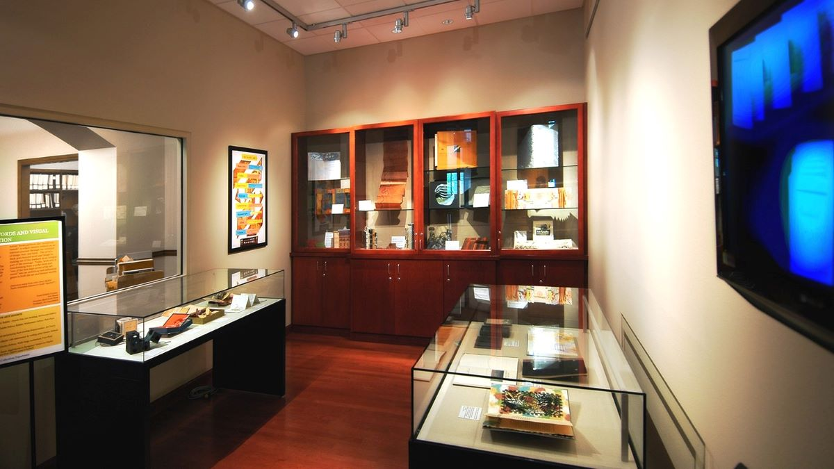 The foyer of the Special Collections and University Archives department with glass and wooden displays showing archival items