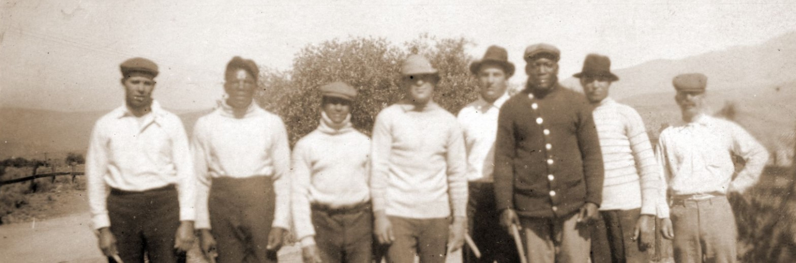 Jack Johnson and his entourage standing in a field with sticks