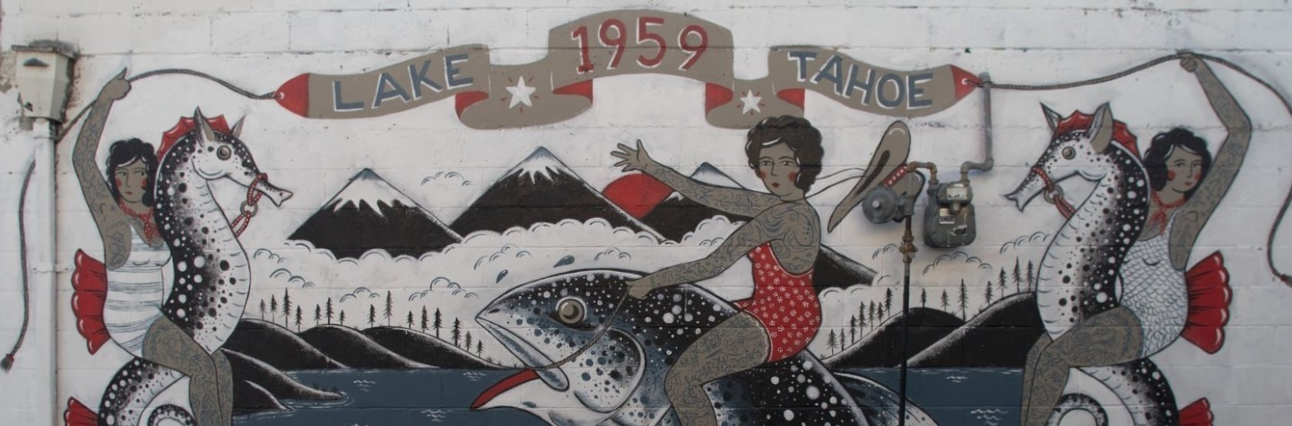 Street art showing a building with women in tattoos and swim suits riding seahorses and fish with a banner that says Lake Tahoe 1959 Queen of the Rodeo