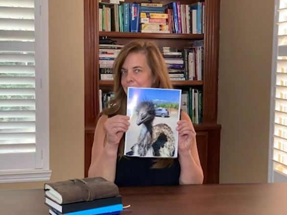 Robin Montieth posing in her office in front of a bookshelf holding an image of an emu