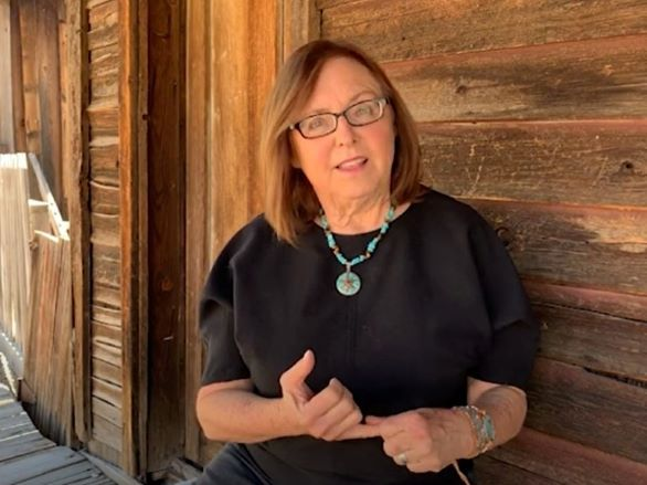 Author and educator Terri Farley in front of a rustic wooden building