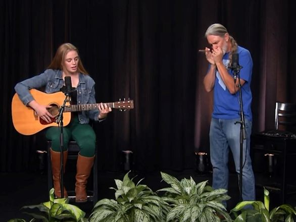 Michael and Hannah Branch playing harmonica and guitar on a stage with ferns
