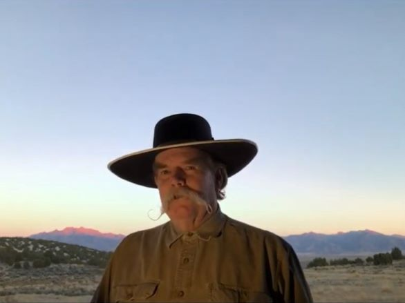 Waddie Mitchell in a cowboy hat with a Nevada outdoor scene in the background